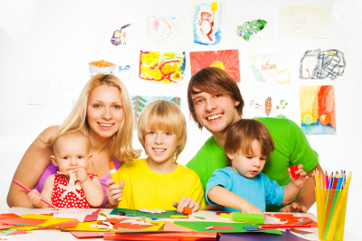 Family of two parents and three kids, little boys and baby girl crafting with paper glue and scissors,